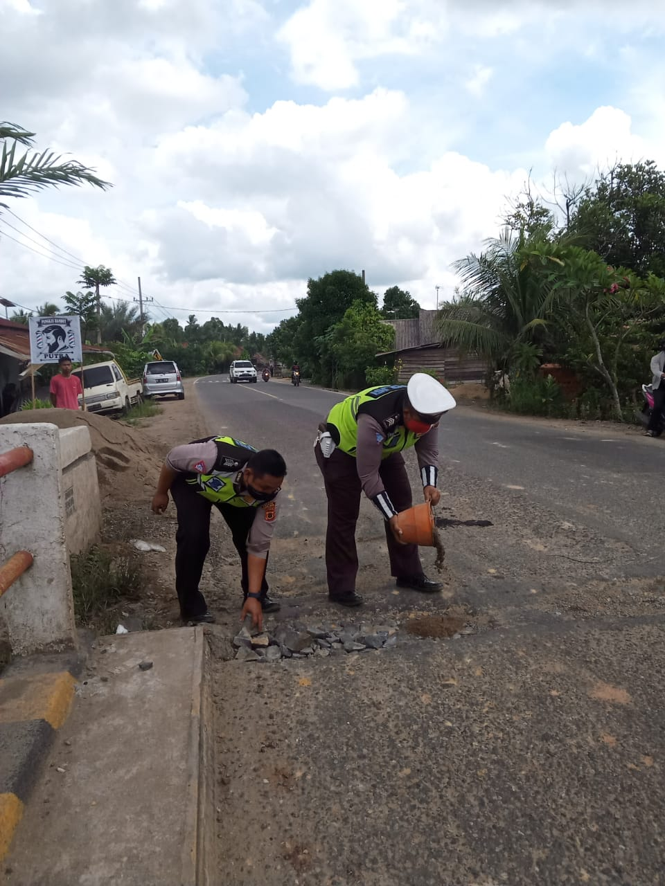 Aksi Bripka Doni dan Bripka Suhendri saat memperbaiki jalan yang berlubang di atas jembatan Desa Berembang.