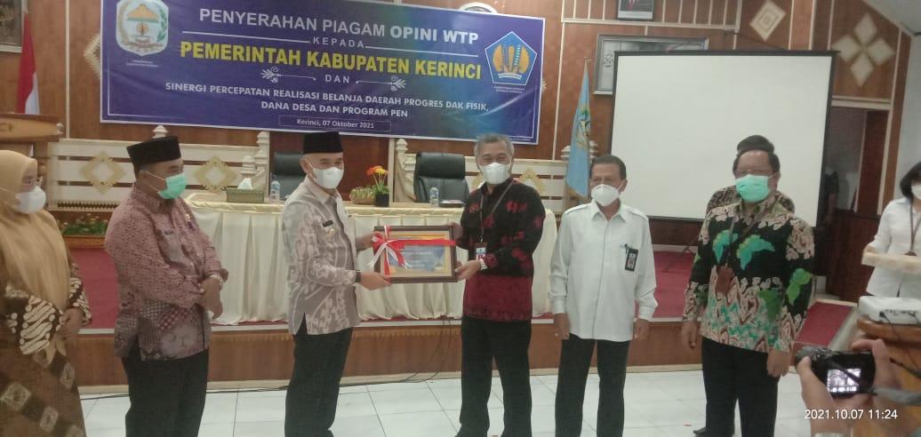 Bupati Adirozal menerima plakat dan piagam opini WTP dari Kepala Kanwil Ditjen Perbendaharaan Provinsi Jambi Supendi.